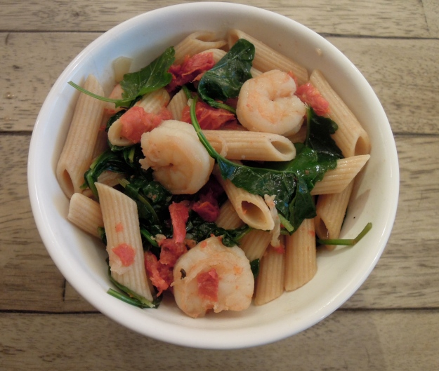 Whole wheat penne, sun dried tomatoes, and greens in a white wine garlic sauce
