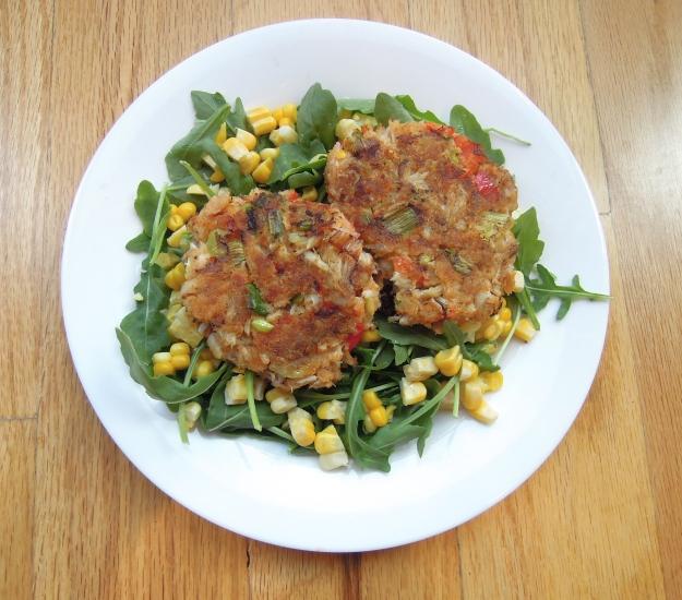 Veggies crab cakes on an arugula salad with corn